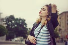 La femme avec un appareil-photo a plaisir à être dans la ville photos stock