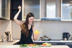 La femme avec un couteau commence à couper le poivre frais photo libre de droits