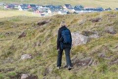 La femme avec un sac à dos marche sur les collines sur les Iles Féroé image libre de droits