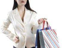 La femme avec un sac dans une veste légère et vont faire des emplettes avec un fond blanc images stock