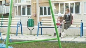La femme avec une petite fille s'assied sur un banc et utilise des instruments banque de vidéos