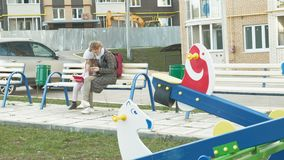 La femme avec une petite fille s'assied sur un banc et utilise des instruments clips vidéos
