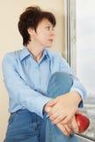 La femme avec une pomme s'assied près d'une fenêtre Image libre de droits