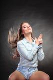 La femme ayant l'amusement feignant le doigt de main est une arme à feu photos stock