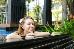 La femme bénéficient du traitement de santé et de beauté en tant qu'ouside de bains d'eau bouillante photo libre de droits