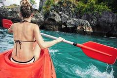La femme barbote le kayak dans le lac avec de l'eau turquoise photos stock