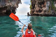 La femme barbote le kayak en mer tropicale photos stock