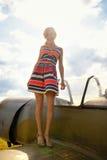 La femme beautyful de mode dans la robe reste sur une aile du vieil avion Photos stock