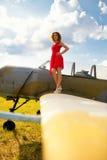 La femme beautyful de mode dans la robe rouge reste sur une aile du vieil avion photos libres de droits