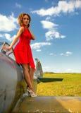 La femme beautyful de mode dans la robe rouge reste sur une aile du vieil avion Photo libre de droits