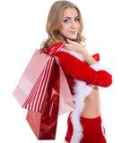 La femme beautyful heureuse dans le père noël rouge vêtx avec des paniers Photos stock