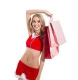 La femme beautyful heureuse dans le père noël rouge vêtx W Photo stock