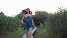 La femme belle de sourire court nu-pieds sur le pont en bois en air ouvert parmi la haute herbe verte banque de vidéos