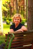 La femme belle s'assied sur un banc et un sourire Image stock
