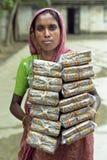 La femme bengali porte des piles des cigarettes dans l'usine photos stock