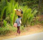 La femme birmanne porte un sac sur sa tête Images stock