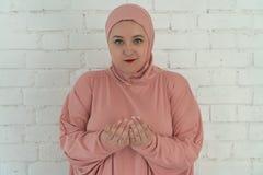 La femme blanche avec des yeux bleus dans un hijab rose prie sur un fond blanc Concept religieux de mode de vie de personnes photographie stock