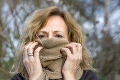 La femme blanche blonde couvre son visage d'écharpe beige de laine laissant seulement les yeux découverts images stock