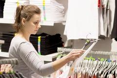 La femme blanche de brune choisit des vêtements dans le magasin Vente dans la boutique de mode Habillez le concept Achetez les no images stock