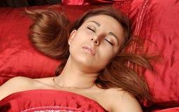 La femme blanche dort sur la toile rouge Photo stock