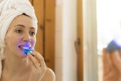 La femme blanchit des dents avec la pâte dentifrice spéciale et la lumière a de LED photo stock