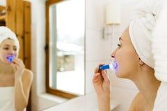 La femme blanchit des dents avec la pâte dentifrice spéciale et la lumière a de LED image stock