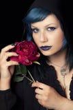 La femme bleue de cheveux de maquillage avec le chapeau noir de capot et s'est levée Photographie stock libre de droits
