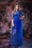 La femme blonde élégante dans la robe de scintillement de soirée bleue pose sur le fond coloré par marbre image stock