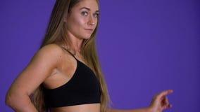 La femme blonde adaptée dans le pantalon de yoga tourne autour et pose banque de vidéos