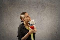 La femme blonde assez jeune en tissus occasionnels se tient dans le jouet de chat de peluche de bras avec le coeur, rêver, recher Images libres de droits
