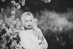 La femme blonde avec composent sur les lèvres rouges en fleurs images libres de droits