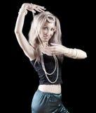 La femme blonde avec de longs cheveux et perle danse une danse orientale sur le fond foncé. Images libres de droits