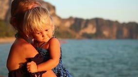 la femme blonde avec le petit enfant admire le coucher du soleil contre des falaises banque de vidéos