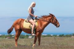 La femme blonde dans la robe à pois monte sur le cheval image libre de droits