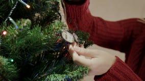 La femme blonde dans le pull rouge décorent l'arbre de Noël avec des cerfs communs de Noël banque de vidéos