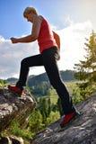 La femme blonde dans s'élever rouge rejette la marche sur les montagnes Images libres de droits