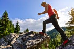 La femme blonde dans s'élever rouge rejette la marche sur les montagnes Image stock