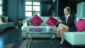 La femme blonde heureuse d'affaires travaille dans la barre ou le café, utilise le comprimé et le téléphone, boit du café, sourir banque de vidéos