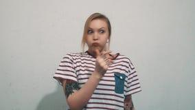 La femme blonde joyeuse dans la chemise rayée avec des tatouages soufflent des joues sur le mur blanc clips vidéos