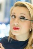 La femme blonde met le mascara aux mèches Image stock