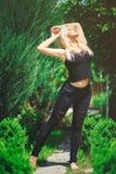 La femme blonde mignonne dans l'équipement noir apprécie le soleil Photo stock