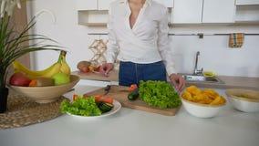 La femme blonde mince accomplit la préparation du petit déjeuner sain et écarte des légumes, se tenant à la table de moderne banque de vidéos