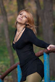La femme blonde mince attirante a avec élégance plié tenir le rail Image libre de droits