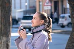 La femme blonde photographie dans un manteau sur la rue Images libres de droits