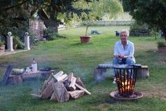 La femme blonde regarde le feu de camp dans le panier de feu images libres de droits