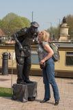 La femme blonde se tient sur la pointe des pieds pour embrasser la statue vivante sur la joue Photos stock