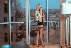 La femme blonde sexuelle mince boit du thé près de la grande fenêtre avec c Photographie stock