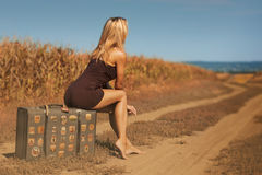 La femme blonde sexy s'assied sur une vieille valise extérieure Photo libre de droits