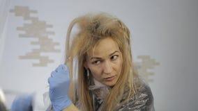La femme blonde teint ses cheveux Cheveux de coloration à la maison banque de vidéos
