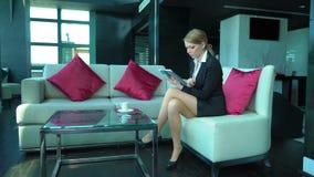 La femme blonde tendue d'affaires travaille dans la barre ou le café, lit le comprimé, utilisations téléphonent, café de boissons banque de vidéos
